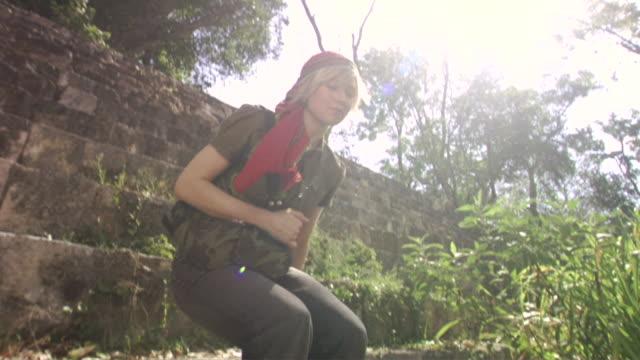 vídeos de stock e filmes b-roll de la ws pan ms woman walking down and sitting on steps at mayan ruins / merida, mexico  - sentar se