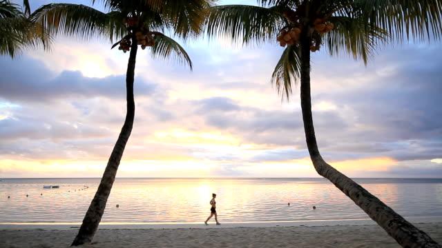 Woman walking down beach by palm trees