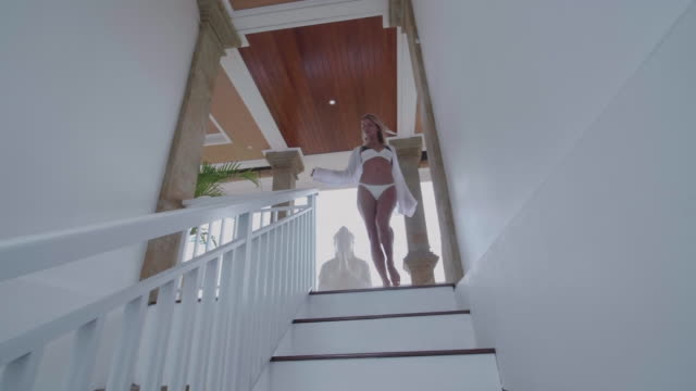 a woman walking down staircase stairs in a bikini at a villa resort hotel traveling in exotic tropical bali, indonesia. - ubud district stock videos & royalty-free footage