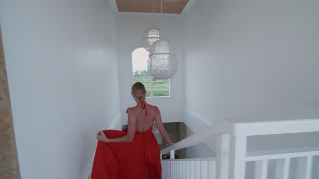woman walking down stairs at a villa resort hotel wearing red dress traveling in exotic tropical bali, indonesia. - slow motion - staircase stock videos & royalty-free footage