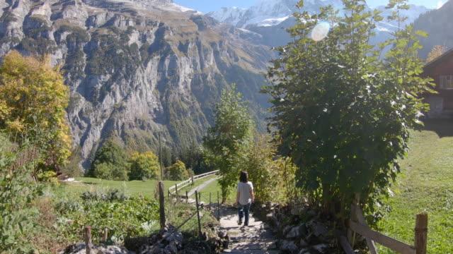 stockvideo's en b-roll-footage met vrouw lopend onderaan de trap door alpine dorp - alleen oudere vrouwen