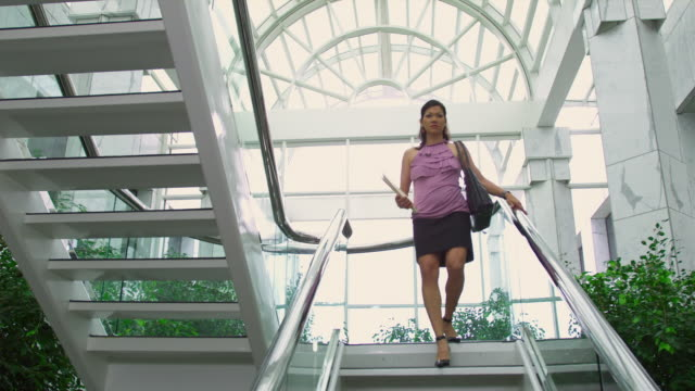 WS LA Woman walking down steps at office park, Austin, Texas, USA