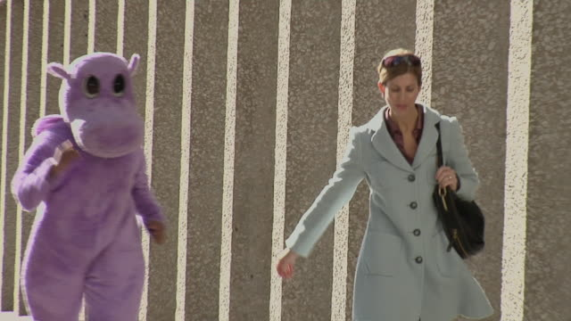 ms, ds, woman walking down street being chased by person in purple hippo suit, dallas, texas, usa - pursuit concept video stock e b–roll