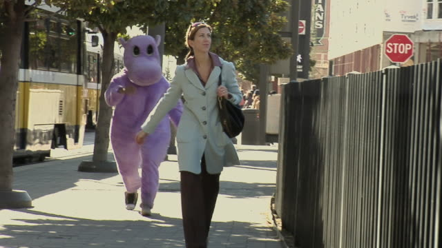 vidéos et rushes de ms, ds, woman walking down street being chased by person in purple hippo suit, dallas, texas, usa - visage caché