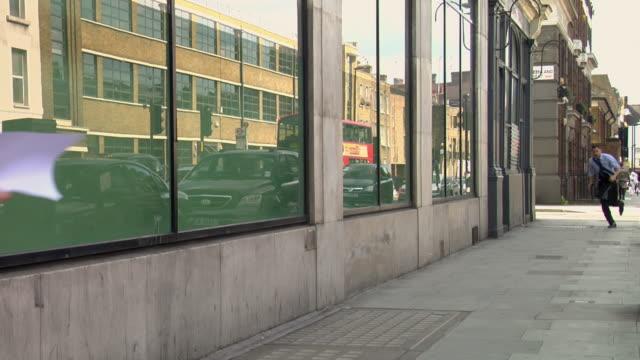 vidéos et rushes de ws woman walking down street being knocked into by man running towards him / london, uk  - heurter