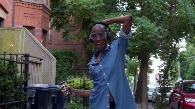 woman walking down street dancing - kamerafahrt auf schienen stock-videos und b-roll-filmmaterial