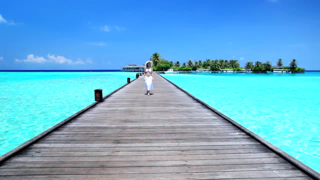 Woman walking in a bridge on the azure water
