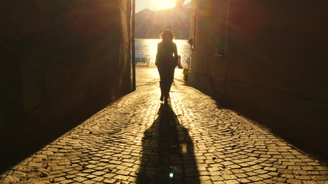 woman walking in a narrow street with sunlight in golden hour - kopfsteinpflaster stock-videos und b-roll-filmmaterial