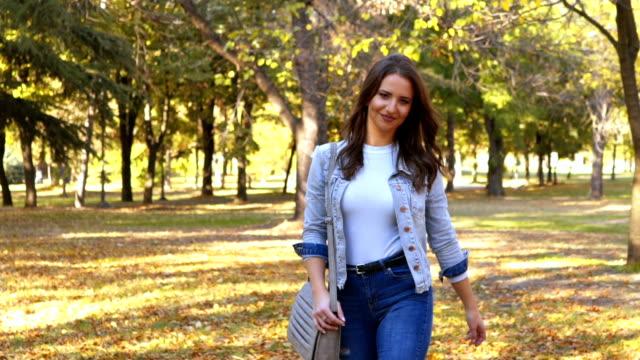 woman walking in a park - denim jacket stock videos & royalty-free footage