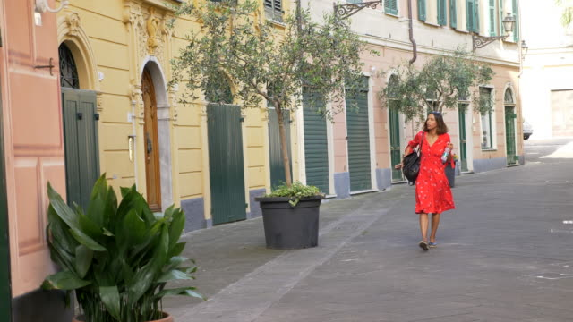 A woman walking in a red dress in a luxury resort town in Italy, Europe. - Slow Motion