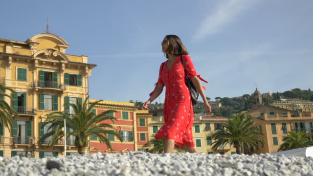 a woman walking in a red dress in a luxury resort town in italy, europe. - slow motion - goodsportvideo stock videos and b-roll footage