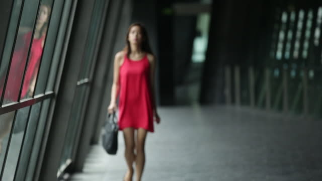 SLO MO Woman walking in a red dress.