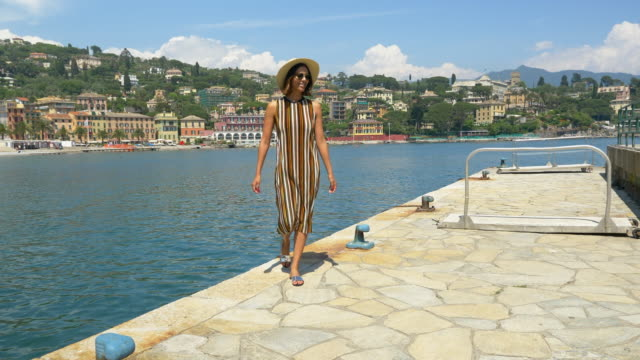 A woman walking in a striped dress and hat in a luxury resort town in Italy, Europe. - Slow Motion