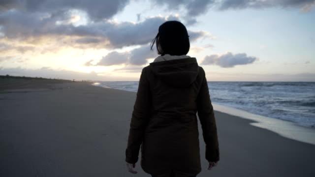 vidéos et rushes de m/s woman walking in an empty beach at sunrise (winter), steadycam backshot - angle de prise de vue