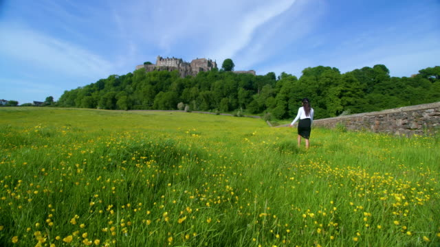 Woman Walking In Buttercup Field In Front Of Stirling Castle, Stirlingshire, Scotland