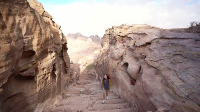 woman walking in canyon in petra - narrow stock videos & royalty-free footage
