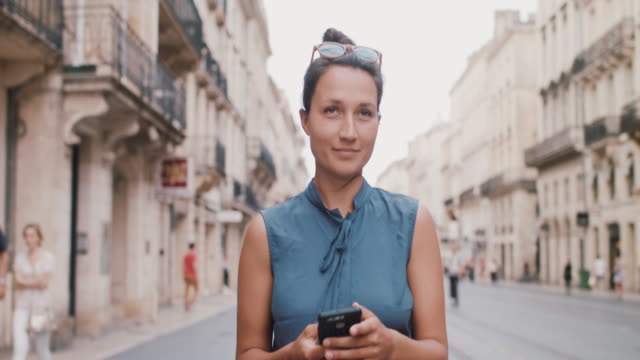 woman walking in european city looking at phone - mobile app stock videos & royalty-free footage