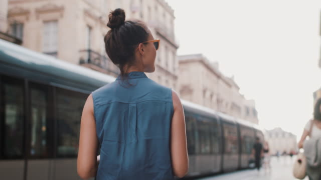 vidéos et rushes de woman walking in european city past tram with cell phone - tramway