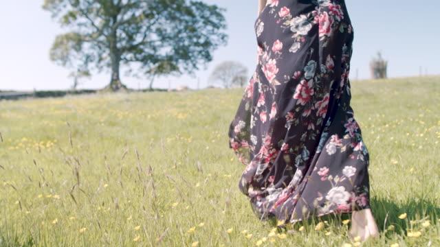 Woman walking in field barefoot in flowery field in summer