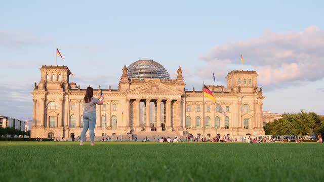 donna che cammina davanti al reichstag e scatta una foto di esso - palace video stock e b–roll