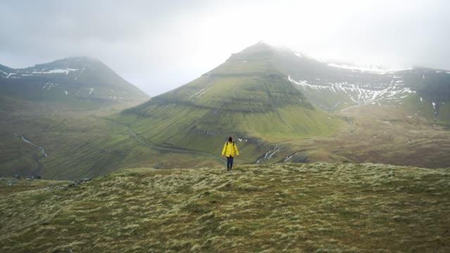 woman walking in mountains on faroe islands - raincoat stock videos & royalty-free footage