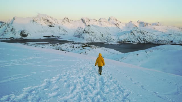 woman walking in mountains on lofoten island in snow - rear view stock videos & royalty-free footage