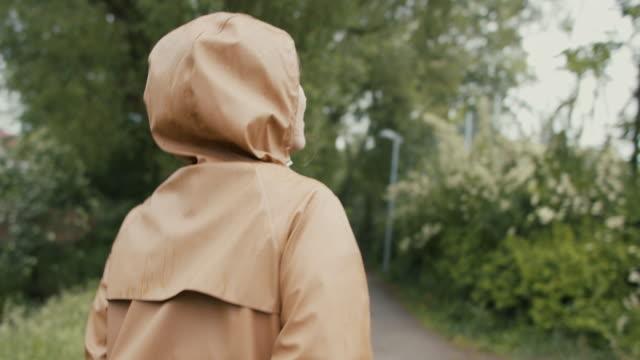 woman walking in nature in rain - レインコート点の映像素材/bロール