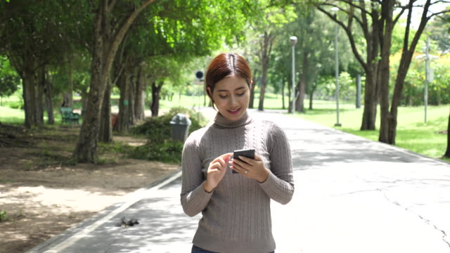 Woman walking in Park and uses smartphone