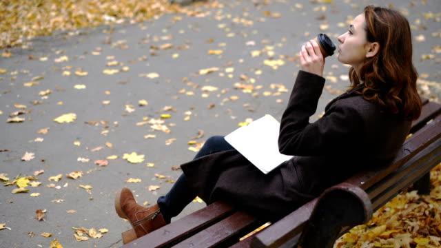 秋の朝の公園で歩いている女性 - 使い捨てコップ点の映像素材/bロール