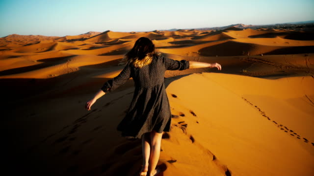 Woman walking in Sahara desert at sunset