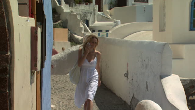 A woman walking in Santorini on her cellular phone