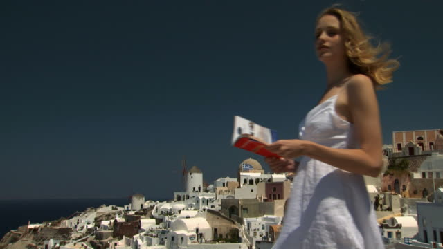 A woman walking in Santorini with a book