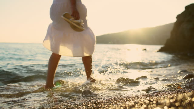 Woman walking in shallow water at sunset