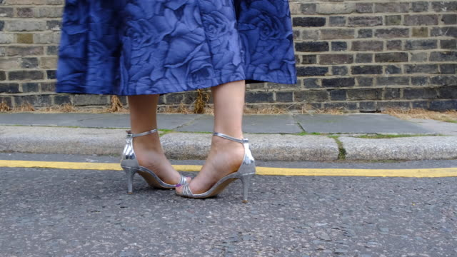 stockvideo's en b-roll-footage met vrouw wandelen in zilverkleur hoge hakken - rok