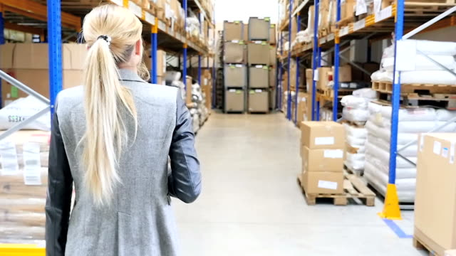 woman walking in storage room - blonde hair stock videos & royalty-free footage