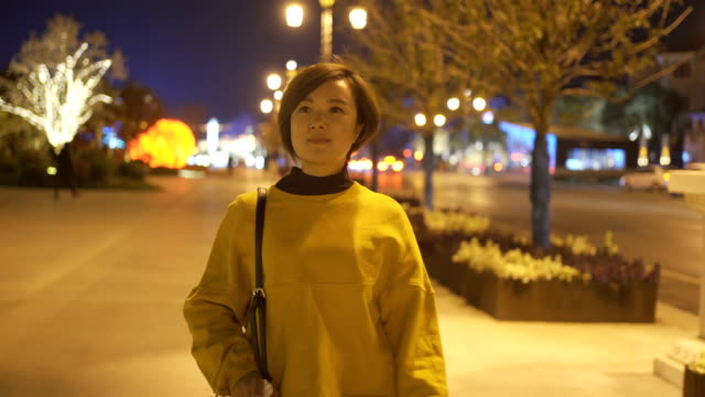 woman walking in street at night - electric lamp stock videos & royalty-free footage