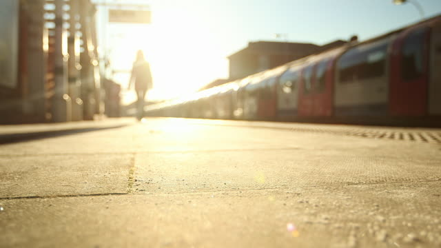 WS Woman walking in sunlight on platform of Epping Underground Station / London, England, United Kingdom