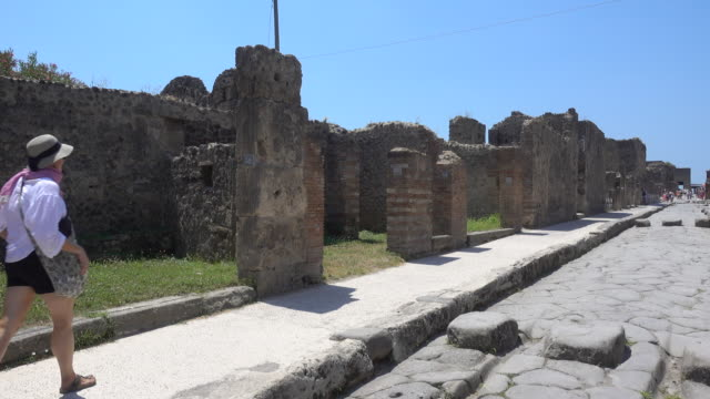 vidéos et rushes de a woman walking in the ancient ruins sightseeing historic landmark of pompeii, italy, europe. - archéologie