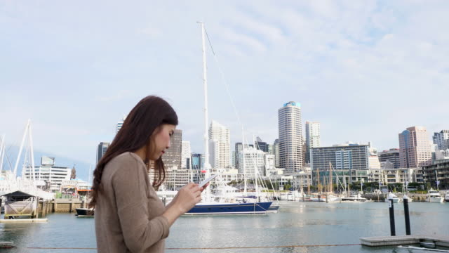 woman walking in the city and uses smartphone - new zealand stock videos & royalty-free footage