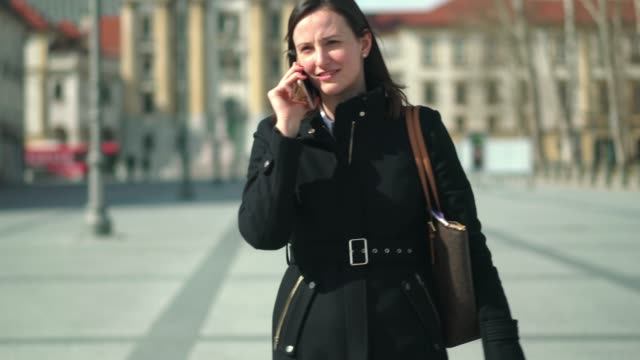 woman walking in the city, on a business call - working on the go - stability stock videos & royalty-free footage