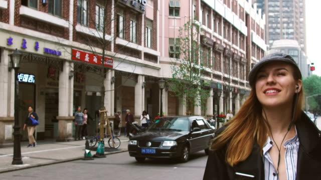 女性の歩行街 - ヘッドフォン点の映像素材/bロール