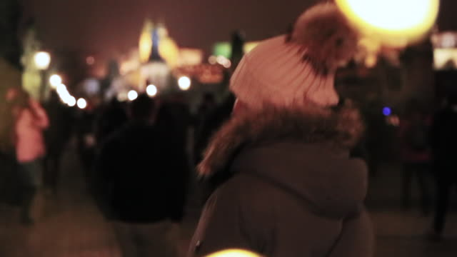 woman walking in the famous charles bridge of prague city at night with crowd people and busy place during travel vacations in the city with the skyline of prague in the background. - winter coat stock videos & royalty-free footage