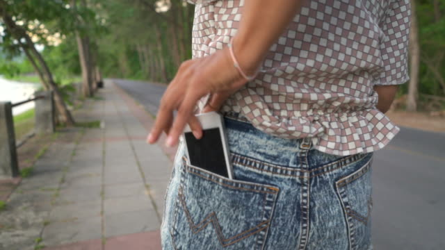 Woman walking in the park and talking on mobile phone, camera stabilizer shot