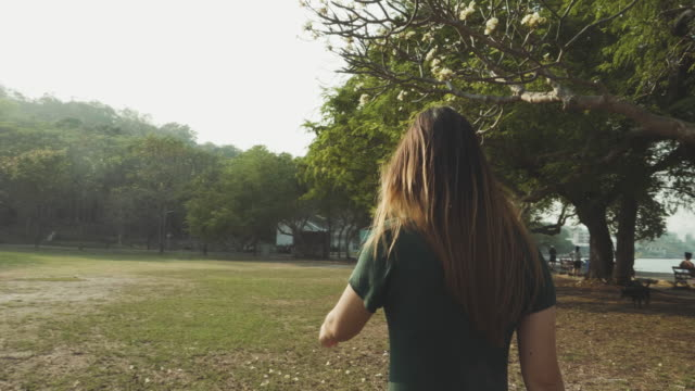 woman walking in the public park at sunset - realisticfilm stock videos and b-roll footage