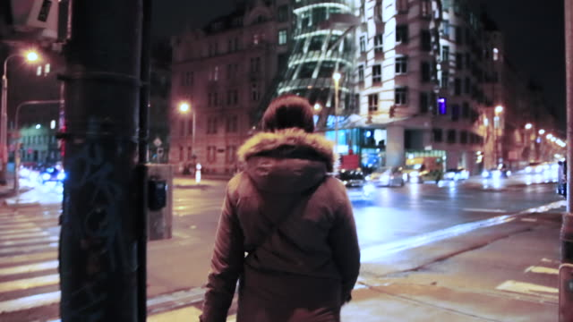 woman walking in the streets of the prague city at night with intersection and busy traffic in the dancing building, a local landmark in prague. - local landmark stock videos and b-roll footage