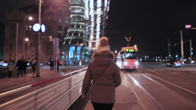 Woman walking in the streets of the Prague city at night with intersection and busy traffic in the Dancing Building, a local landmark in Prague.