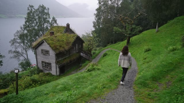 woman walking in  village near the fjord in norway - traditionally norwegian stock videos & royalty-free footage