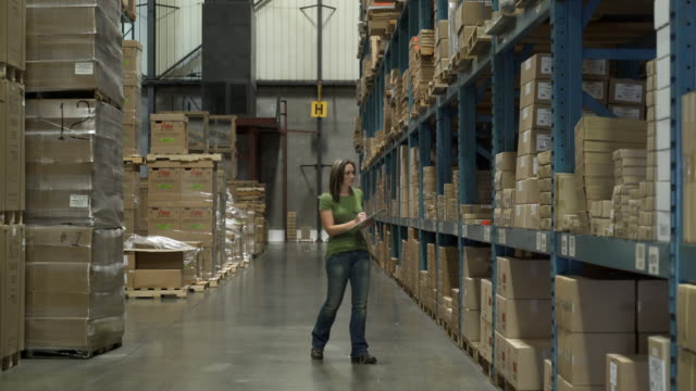 Woman walking in warehouse aisle, holding clipboard and stock taking