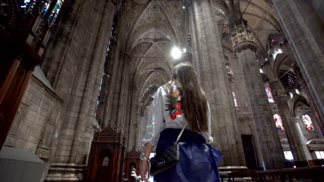 woman walking inside the milan cathedral - cristianesimo video stock e b–roll