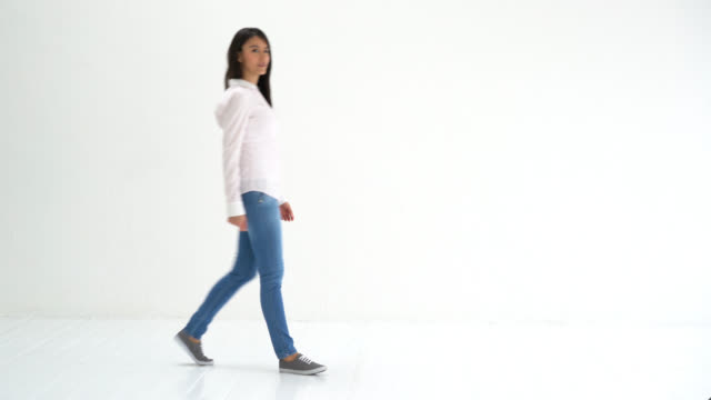 woman walking into a white background studio and showing something - white background stock videos & royalty-free footage